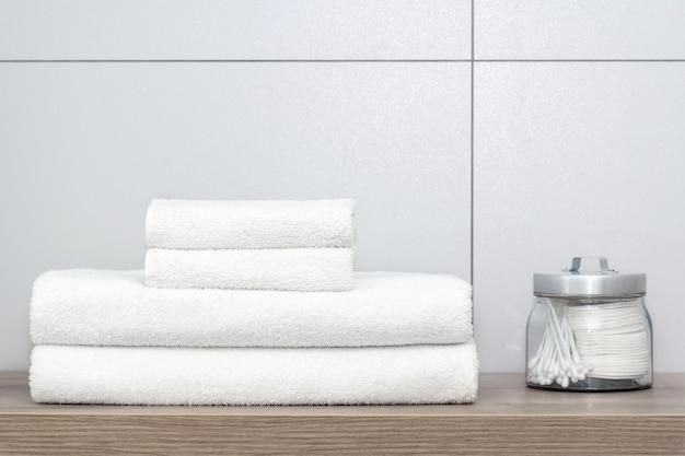Quatre serviettes blanches de différentes tailles, soigneusement pliées, reposent sur une étagère en bois. à côté se trouve une boîte de conserve avec des cotons-tiges et des colliers d'oreille contre un carreau de céramique. Photo Premium