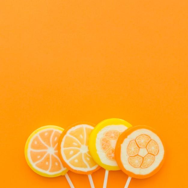 Quatre sucettes aux agrumes au fond d'un fond orange Photo gratuit