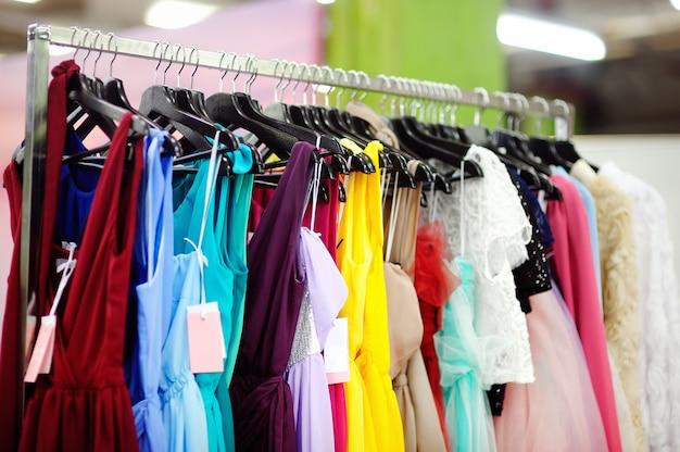 Quelques belles demoiselles d'honneur ou robes du soir sur un cintre dans un magasin de mariage Photo Premium