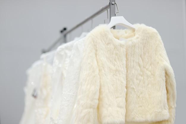 Quelques belles robes de mariée et manteau de fourrure sur un cintre. achats de mariée Photo Premium
