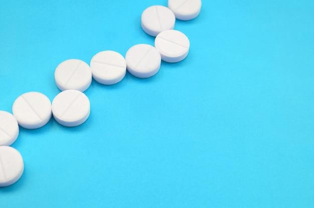 Quelques comprimés blancs se trouvent sur une surface de fond bleu vif Photo Premium