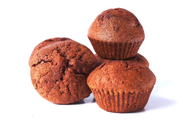 Quelques muffins à la pâte au chocolat noir sur isolé sur fond blanc. Photo Premium