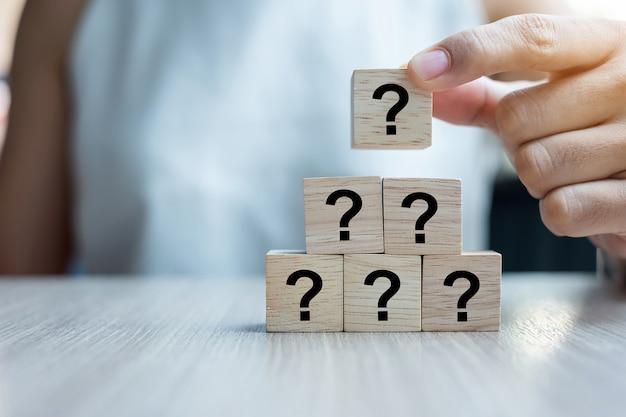 Question De La Femme D'affaires Posant Le Mot Questions (?) Avec Un Cube En Bois Photo Premium