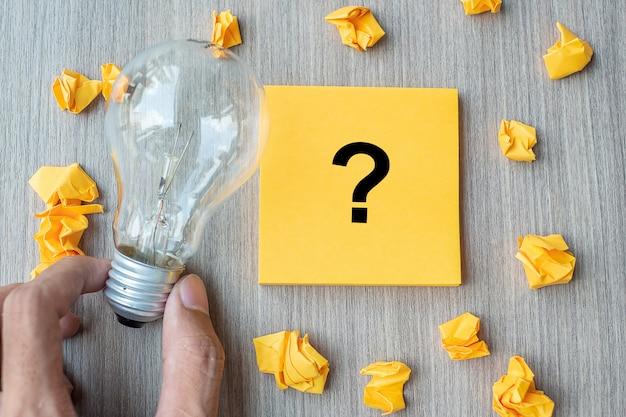 Questions marque (?) mot sur une note jaune et un papier émietté Photo Premium