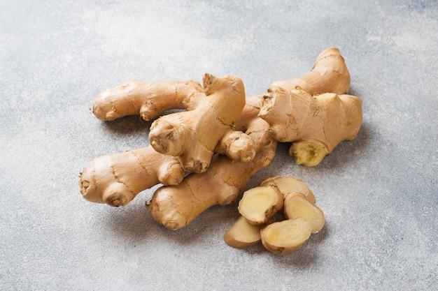 Racine de gingembre frais sur une surface grise. . Photo Premium