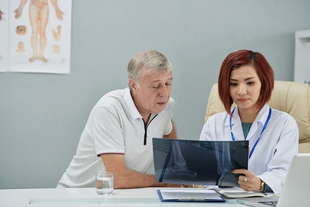 Radiologue montrant une radiographie Photo gratuit