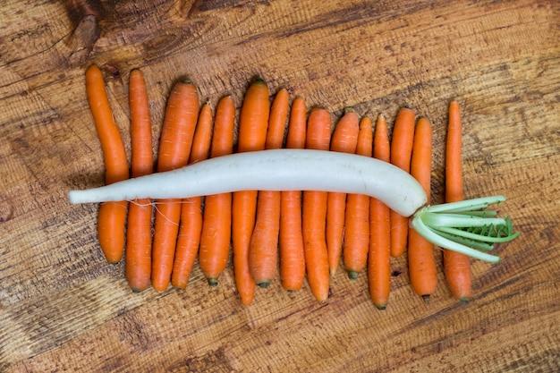 Radis de daikon sur les carottes, fond en bois Photo gratuit