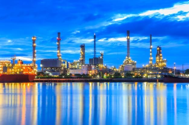 Raffinerie de pétrole le long du fleuve au crépuscule (bangkok, thaïlande) Photo Premium