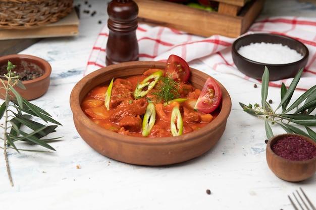 Ragoût de pommes de terre à la viande avec sauce tomate et poivre dans un bol en terre cuite. Photo gratuit