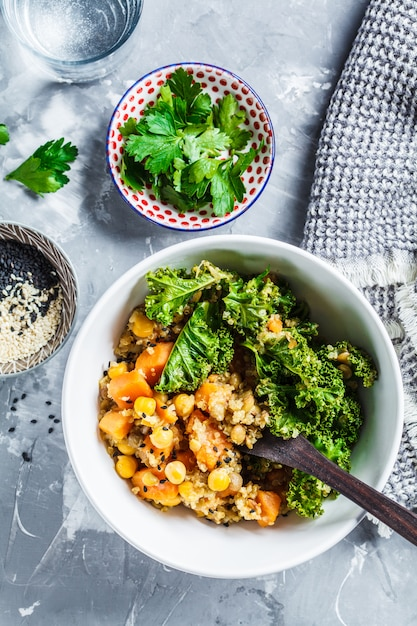 Ragoût végétalien avec pois chiches, patate douce et chou frisé dans un bol blanc, vue de dessus. Photo Premium