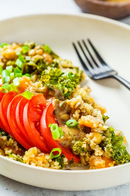 Ragoût végétalien avec pois chiches, patates douces et tomates fraîches sur une plaque blanche. Photo Premium