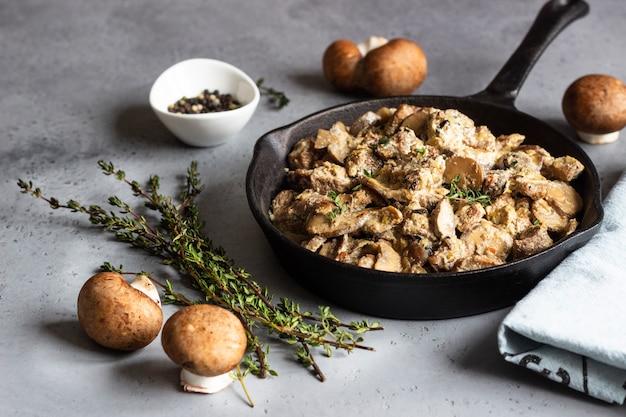 Ragoût de viande avec champignons et thym dans une poêle en fonte Photo Premium