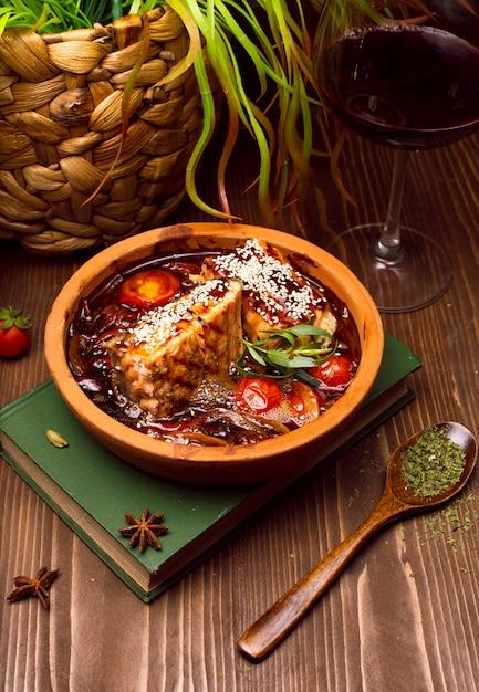 Ragoût de viande avec légumes, tomates. soupe de goulache sur un livre Photo gratuit