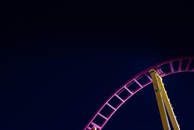 Rails d'un montagnes russes, fond de ciel bleu nuit. Photo Premium