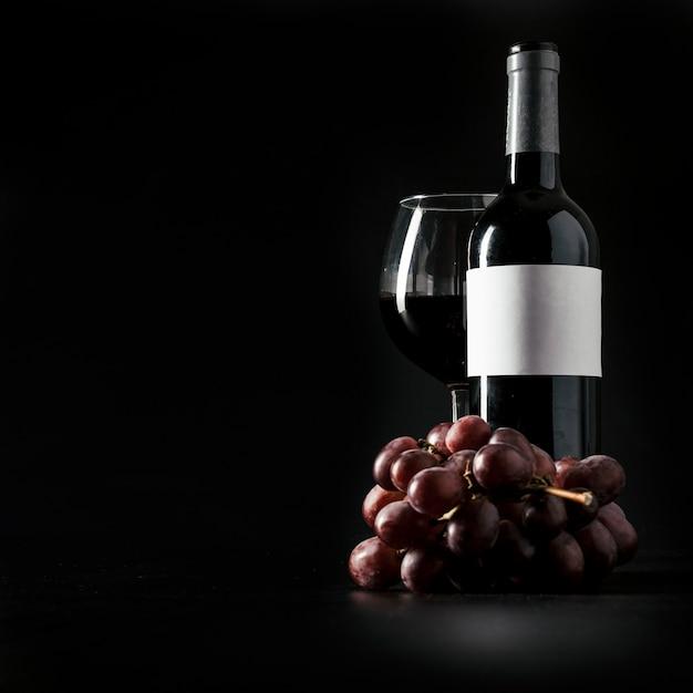 Raisin près de la bouteille et un verre de vin Photo gratuit