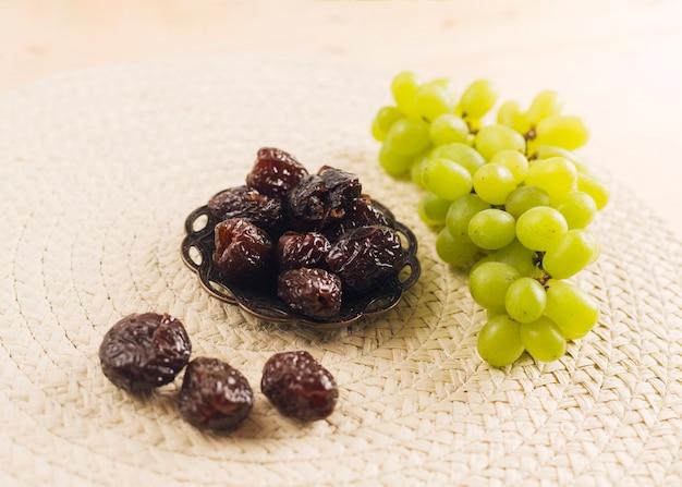 Raisin vert frais près de pruneaux sur soucoupe Photo gratuit