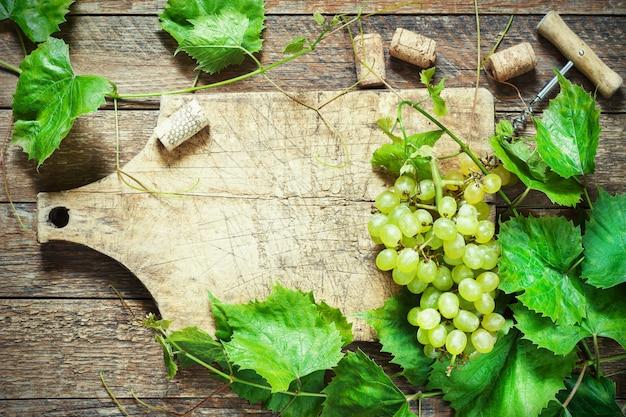 Des Raisins, Une Bouteille De Vin, Des Bouchons En Liège Et Tire-bouchon Sur Une Vieille Table En Bois, De Style Rustique Photo Premium