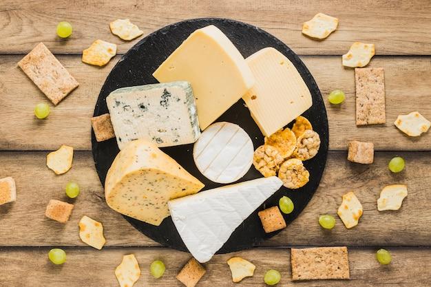 Raisins, craquelins, pain croquant et blocs de fromage sur une ardoise ronde au-dessus du bureau en bois Photo gratuit