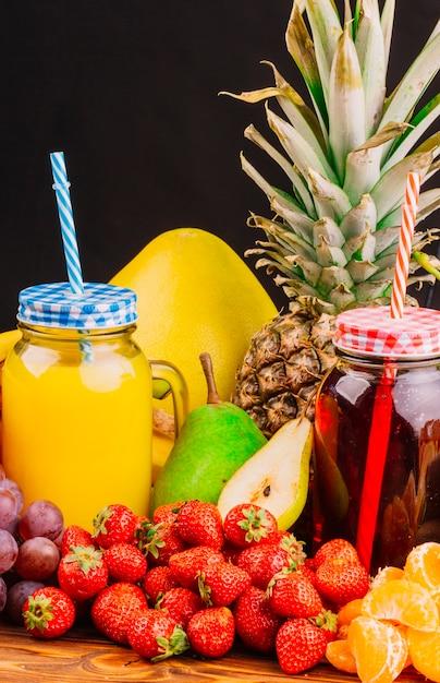 Les raisins; des fraises; poires; bouteille d'ananas et de jus sur fond noir Photo gratuit