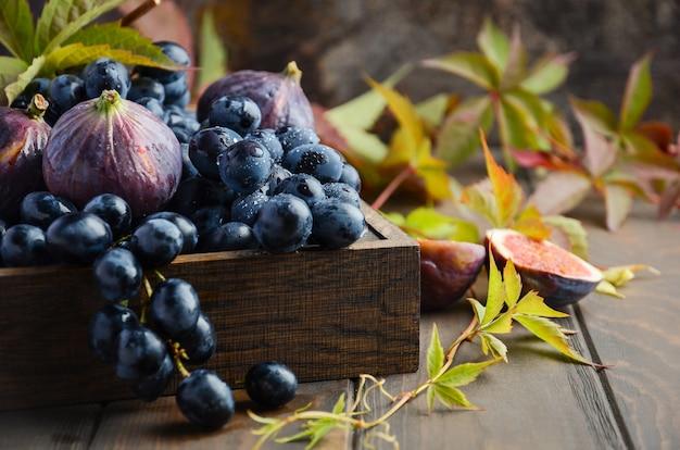 Des raisins noirs frais et des figues dans un plateau en bois foncé sur une table en bois Photo Premium
