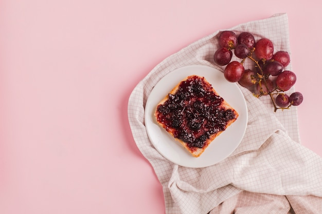 Des raisins rouges et une tranche de pain avec de la confiture sur une assiette blanche sur la nappe sur fond rose Photo gratuit