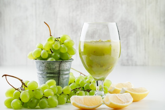 Raisins Verts Avec Des Tranches De Citron, Cocktail De Raisins Dans Un Mini Seau Sur Une Surface Blanche Photo gratuit
