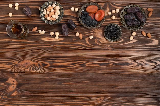 Ramadan dattes fraîches; fruits secs; noix et verre à thé à base de plantes sur un bureau en bois Photo gratuit