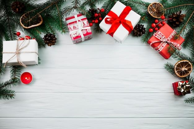 Rameau de noël avec bougie et boîtes à cadeaux Photo gratuit