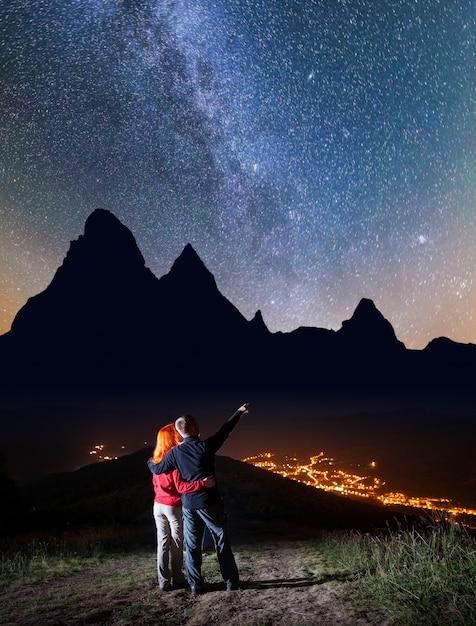 Randonneur homme étreignant fille rousse et montre sur les étoiles Photo Premium