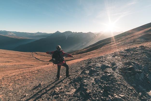 Randonneur homme se détendre au coucher du soleil au sommet de la montagne et en regardant le panorama majestueux des alpes italiennes Photo Premium