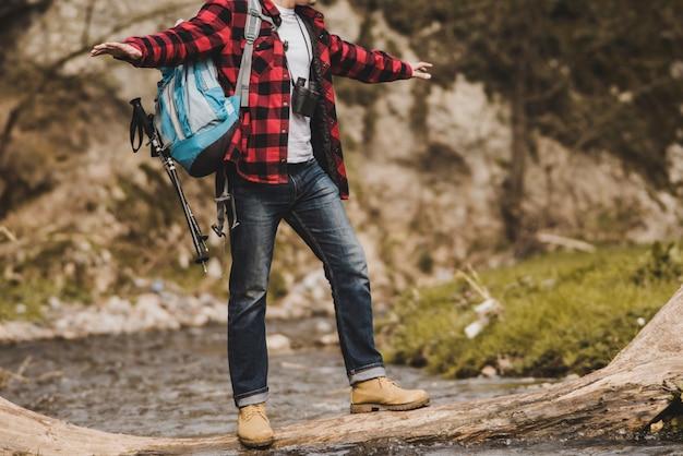 Le randonneur maintient l'équilibre dans la rivière Photo gratuit