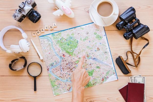 Randonneur pointant sur l'emplacement sur la carte avec une tasse de thé et accessoires de voyageur sur fond en bois Photo gratuit