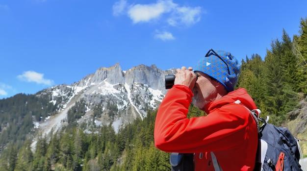 Randonneur en regardant des jumelles dans un paysage de montagne Photo Premium