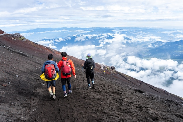 Randonneurs grimpant sur le sentier yoshida du mont fuji en saison d'escalade Photo Premium