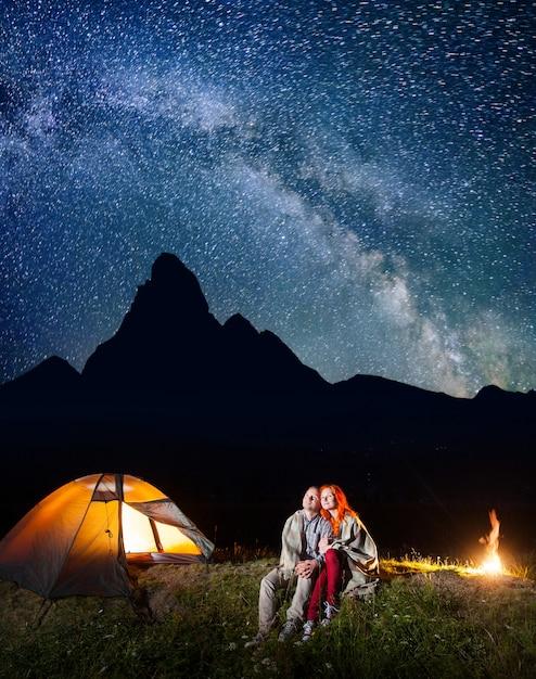 Randonneurs près du feu de camp et tente rougeoyante la nuit sous les étoiles Photo Premium