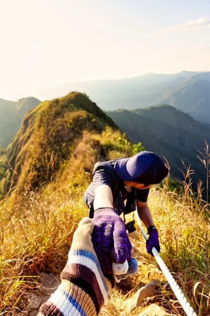Les Randonneurs Se Tiennent La Main En S'aidant à Peine à Gravir La Montagne. Photo Premium