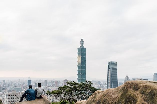 Randonneurs touristiques assis sur des pierres et voyant le gratte-ciel de taipei 101 depuis la montagne d'éléphant de xiangshan dans la soirée à taipei, taiwan. Photo Premium