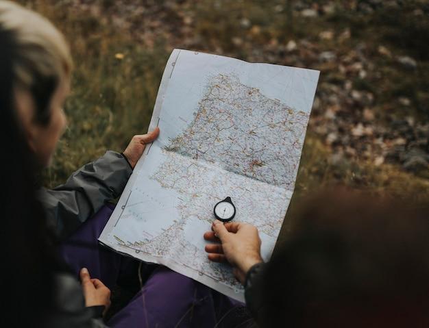 Randonneurs utilisant une boussole et une carte Photo gratuit