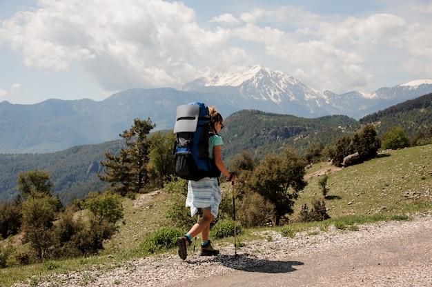 Randonneuse monte la route dans les collines Photo Premium