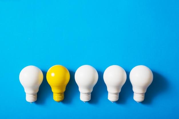 Rangée D'ampoules Blanches Avec Une Ampoule Jaune Sur Fond Bleu Photo gratuit