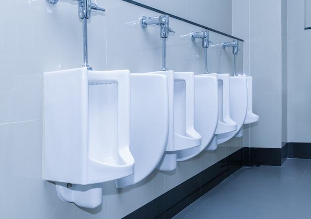 Rangée de blocs sanitaires d'urinoirs dans les toilettes publiques Photo Premium