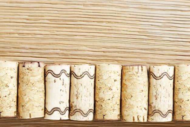 Une rangée de bouchons de vin utilisés sur une vieille table en bois. Photo Premium
