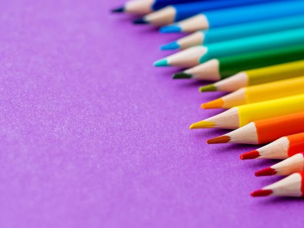 Rangée de crayons d'aquarelle colorés sur lilas. Photo Premium