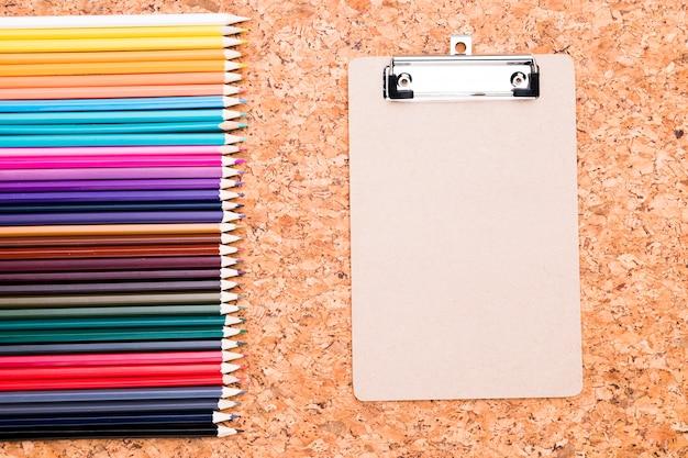 Rangée de crayons de couleur et du presse-papiers sur un fond de liège Photo gratuit