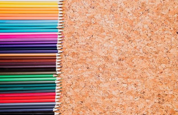Rangée de crayons de couleur sur la vue de dessus du fond de liège Photo gratuit