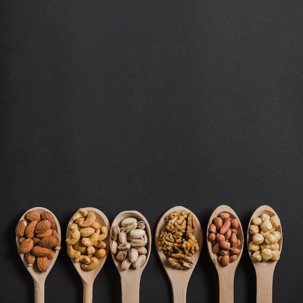Rangée de cuillères avec des noix Photo gratuit