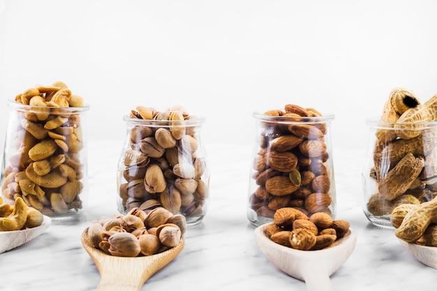 Rangée De Divers Aliments Aux Noix Fraîches Dans Une Cuillère Et Un Bocal En Verre Photo gratuit