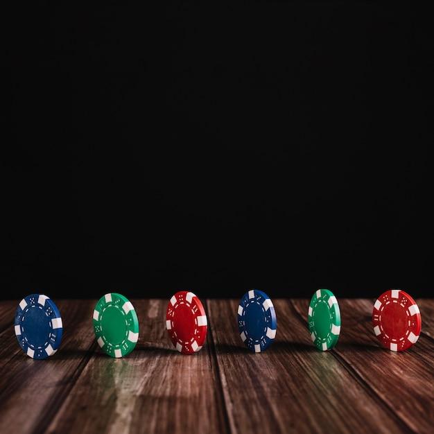 Rangée de jetons de casino colorés sur une surface en bois Photo gratuit