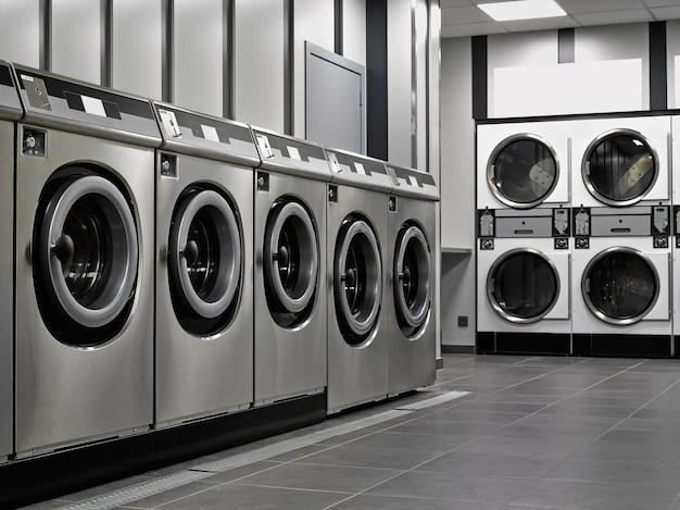 Une rangée de machines à laver industrielles dans une laverie publique Photo Premium
