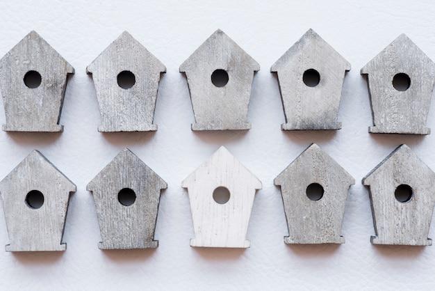 Rangée de maisons d'oiseaux en bois sur fond texturé blanc Photo gratuit